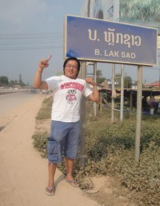 "Pao Vue stands by a sign that says ""Laksao"" wearing a Wisconsin Badgers t-shirt."