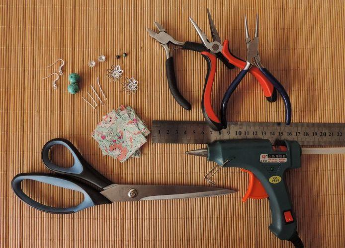 Materiale necesare: 10 pătrate de mătase de 3x3 cm, foarfecă, pistol de lipit cu silicon, patenți, 2 mărgele semiprețioase mari și 2 mici, 2 ace cu buclă, 2 ace cu cap, 4 căpăcele mici și 2 căpăcele mari metalice, o pereche de tortițe pentru cercei
