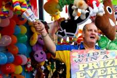 Warren Blasich, 50, a Broadway actor and tv producer from New York, advocates educational excellence and gives prizes to all kids with a passion for learning on Saturday, October 7, 2017 in Perry, Georgia. Blasich takes months of out his year to work at friends' booths at fairs across the nation; he is the only showman that wears a sign and rings a cowbell. (Photo/Reynolds Rogers)