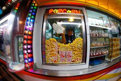 Jean Le Roux, 22, of Cape Town, South Africa, wipes oil off the inside window of the popcorn machine during closing time at the Georgia National Fair in Perry, Georgia on Saturday, October 7, 2017. (Photo/Steffenie Burns)