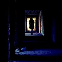 Kobieta w piwnicy płaszcz nogi długie włosy