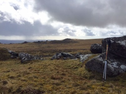 moorland with 2 walking poles propped against a stone