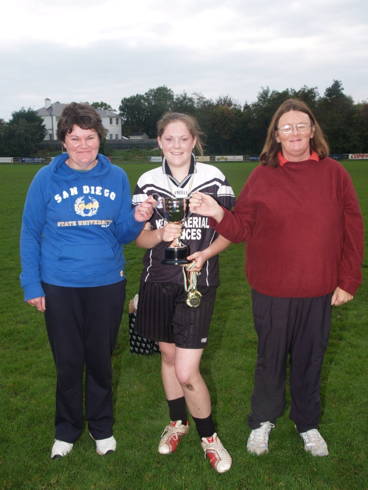 Grainne Mhaols Captain , Noreen Coyne poses with the West Galway U17B Championship Cup alongside Grainne Mhaols LGFA  Honorary Presidents, Mary Coyne and Ann Flaherty.