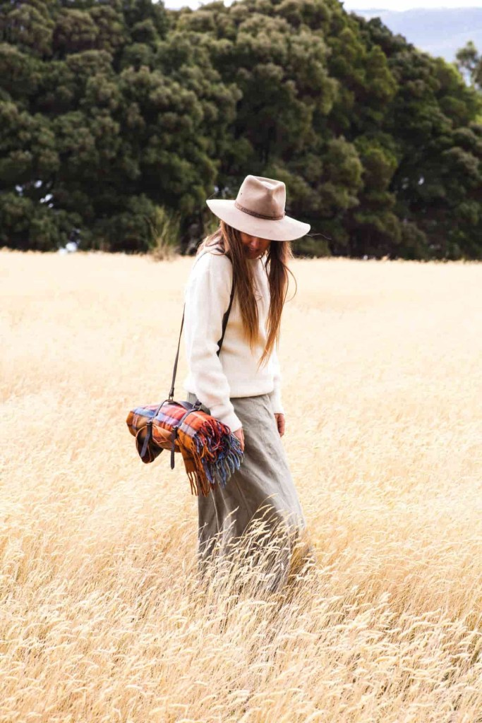 sarah glover walking in field with GGco. picnic blanket
