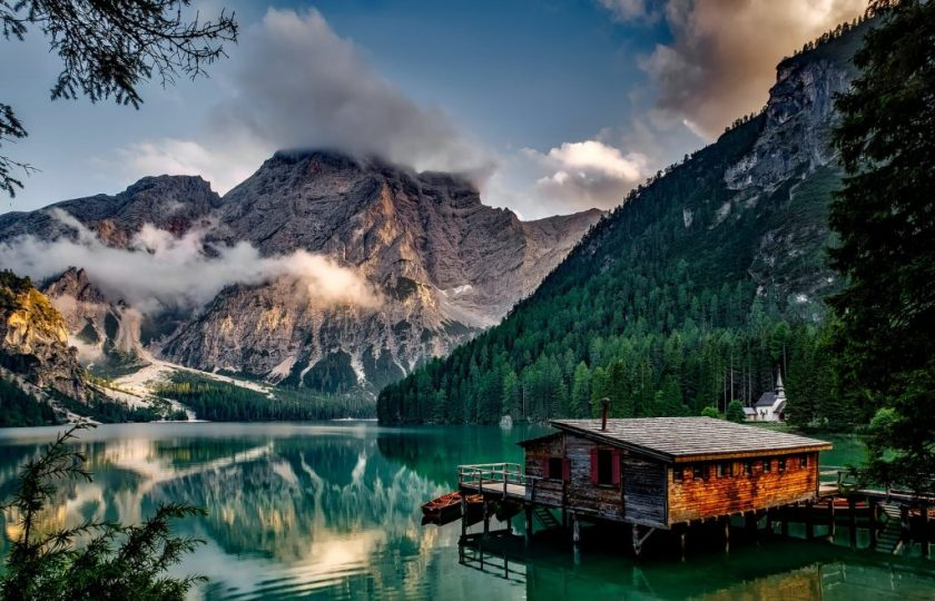 mirror lake reflecting wooden house in middle of lake overlooking mountain ranges