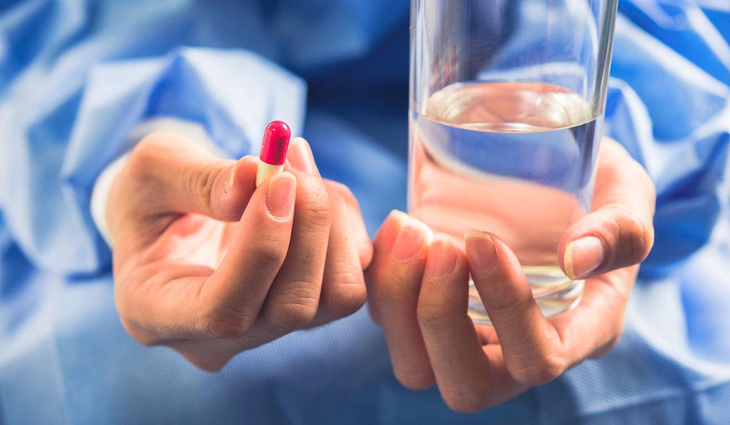 Kapsułka i szklanka wody - Działanie leku nootropowego Encephabol (pyritinol)