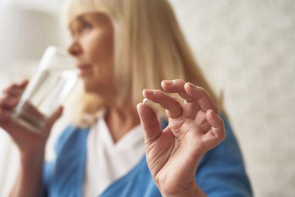 Kobieta łykająca pigułkę - Przeciwdepresyjny suplement 5-HTP