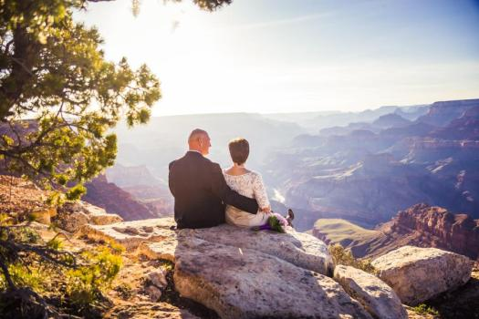 grand canyon wedding bride and groom sitting on the edge