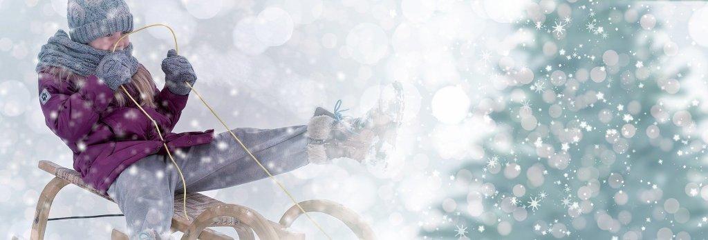 enfant sur une luge, paysage d'hiver