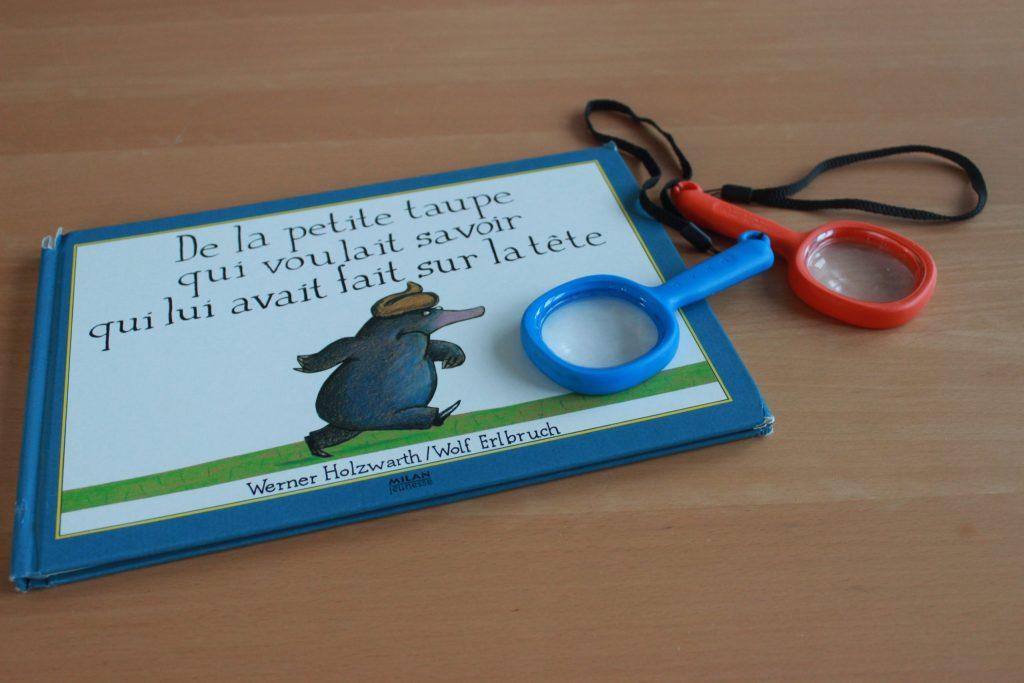 livre de la petite taupe qui voulait savoir qui lui avait fait sur la tête accompagner de deux loupes.