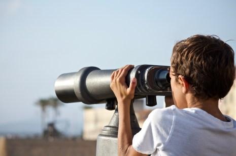 enfant qui observer le paysage avec des grandes jumelles