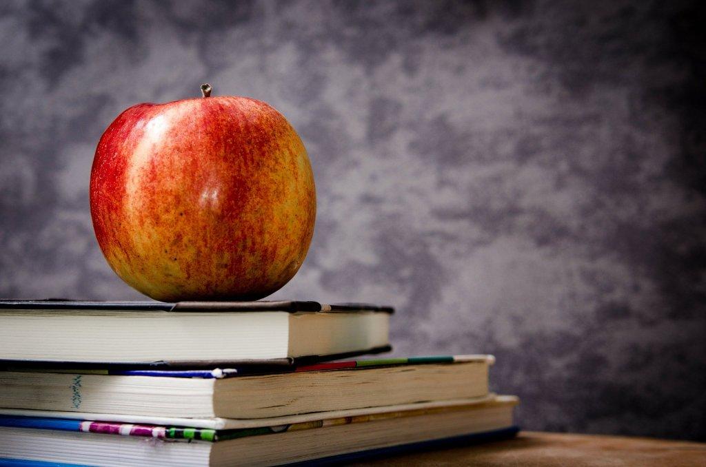 une pomme posée sur des livres