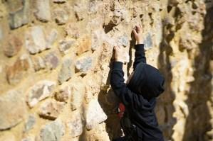 un enfant qui recommence d'escalader un mur après un échec