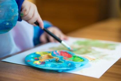 un bébé en train de créer une peinture