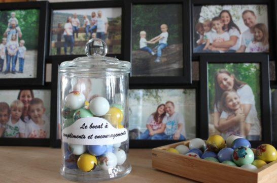 bocal à encouragement et compliments devant un cadre de photos de famille.