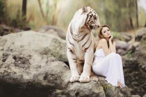 Un tigre blanc et une femme vêtue de blanc en pleine nature
