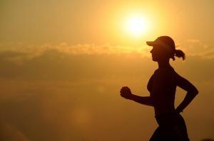 Une femme qui court avec le levée de soleil