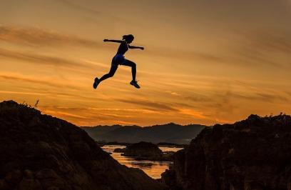 Femme qui saute d'une colline à une autre avec la mer en fond d'image.