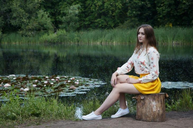 Une fille paisible au bord d'un étang