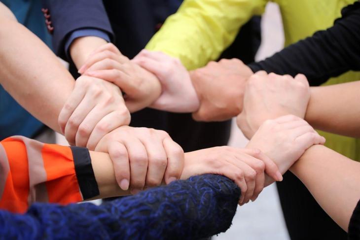 8 personnes se tenant le poignet droit