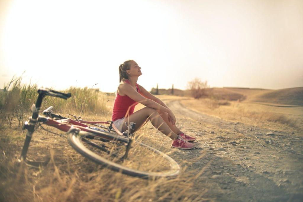Une fille assise dans le sable avec son vélo