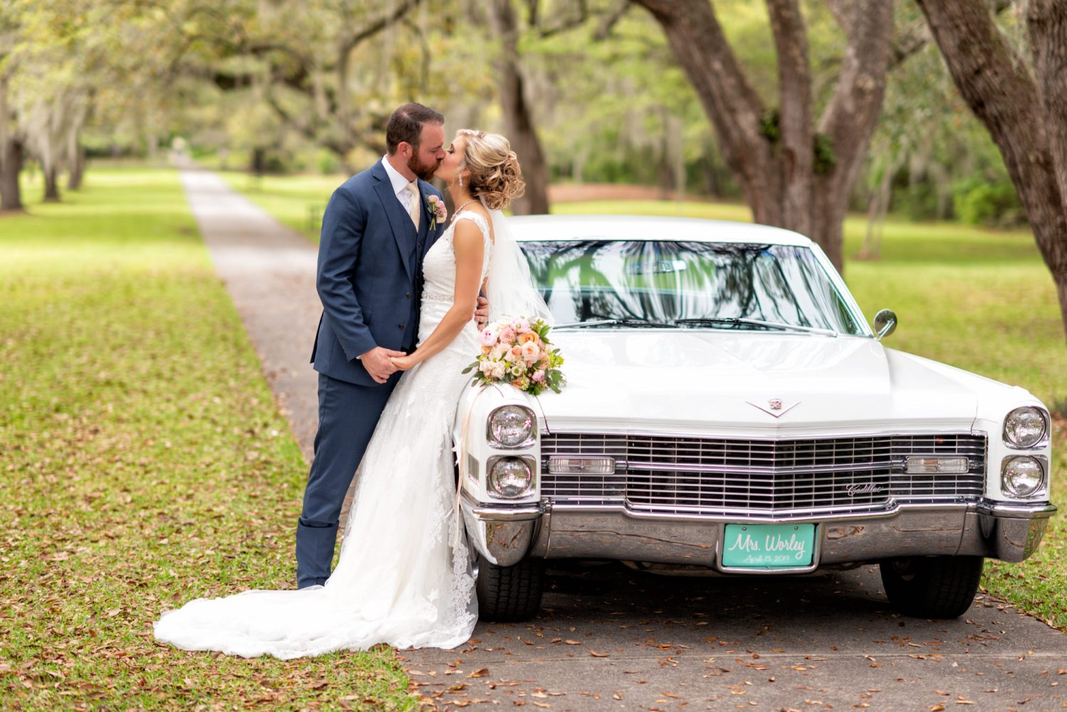 Bride and groom kissing by a classic car -