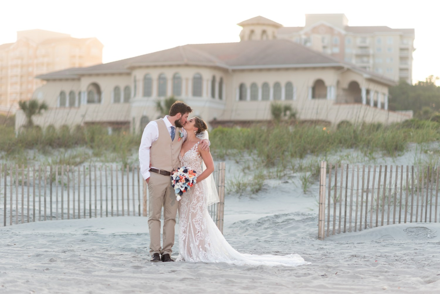 Bride and groom with the clubhouse in the background - Grande Dunes Ocean Club - Myrtle Beach