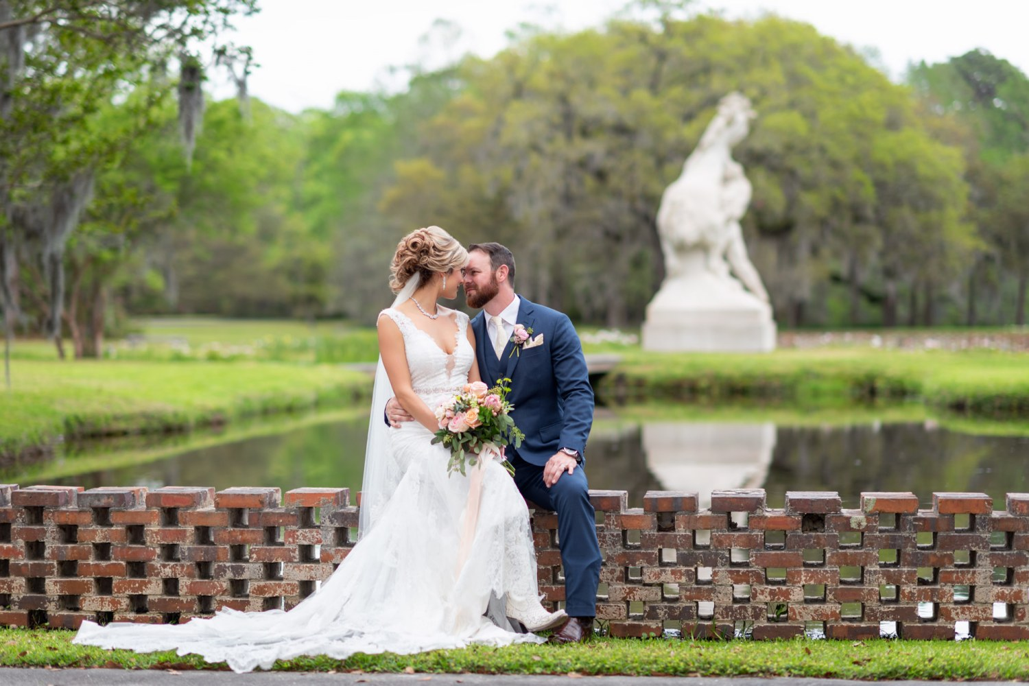 "Bride and groom with ""Youth Taming the Wild"" sculpture in the background - Brookgreen Gardens"