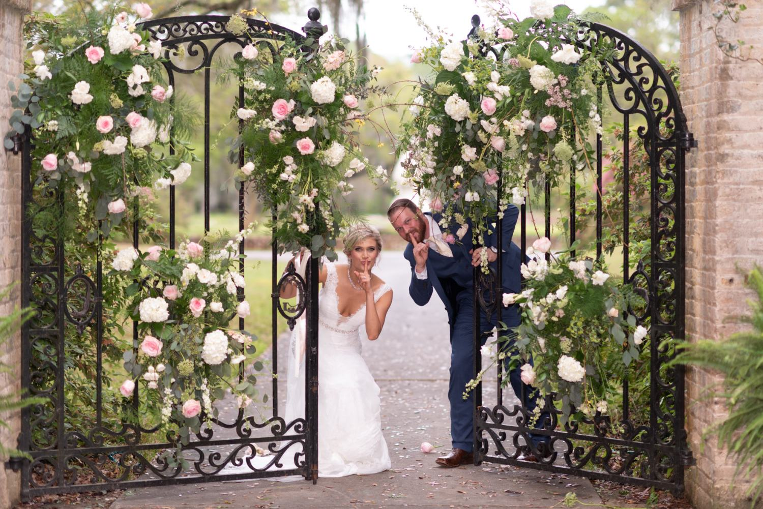 Groom and bride having fun by the gates - Brookgreen Gardens