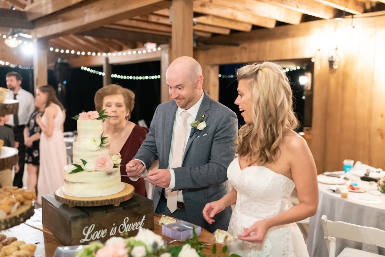 Bride and groom having fun with the cake cutting - Wildhorse at Parker Farms