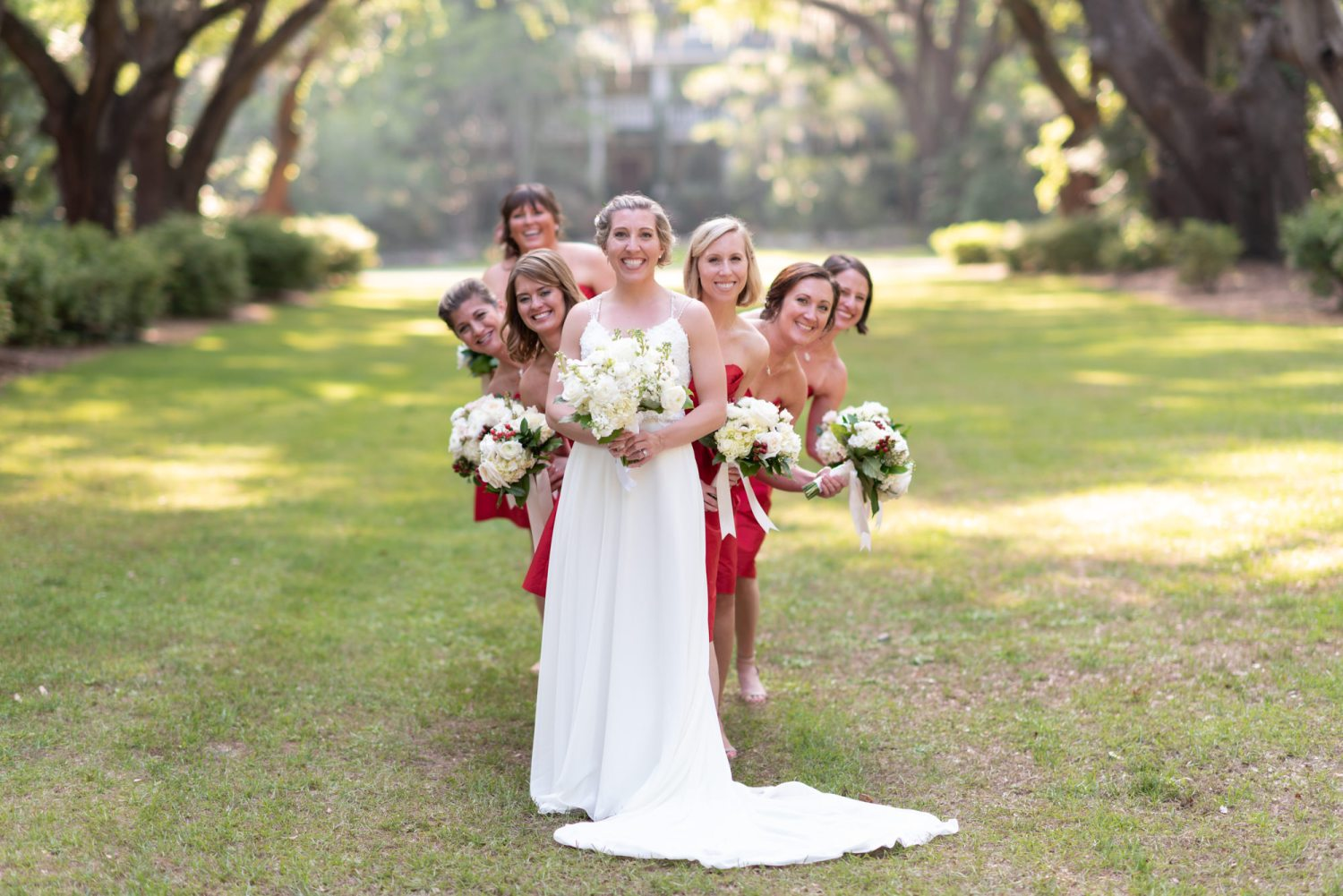 Bridesmaids peeking out from behind the bride - Wachesaw Plantation