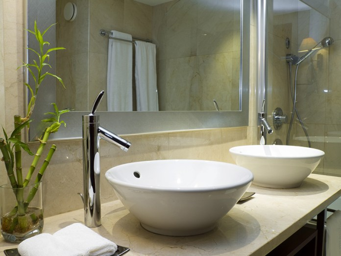 green bathroom with bowl sinks