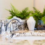 Closeup Of Modern Bathroom Sink With Neutral Granite Countertop And Mirror Green Plant In Pot Granite Liquidators