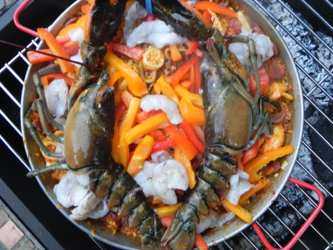 The seafood paella, cooking on the fire. The lobster and shrimp were added at the end. Once you've added the lobster, you can cover with tin foil and finish cooking on the stove top so that it is easier to prepare for serving.