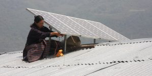 woman installing a rooftop solar panel