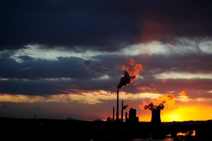 Coal power station with smoking chimneys in sunset