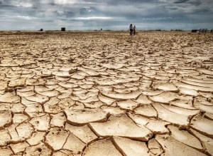 landscape with dry, cracked earth and no plants growing. people walking in distance
