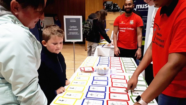 Women and boy standing in front of the carbon calculator table, which is laid with different cards.