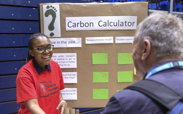 Two people talking and smiling, standing in front of the carbon calculator game