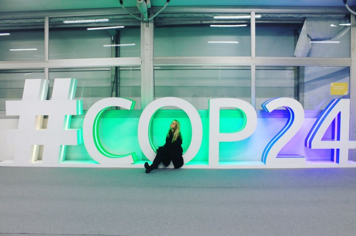 Albertine Pegrum-Haram sitting by the COP24 letters outside the climate summit in Poland