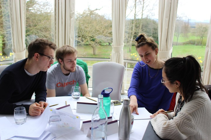 4 students sitting around a table discussing work