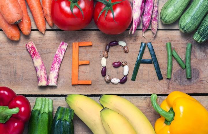 vegan word on wood background and vegetable - food