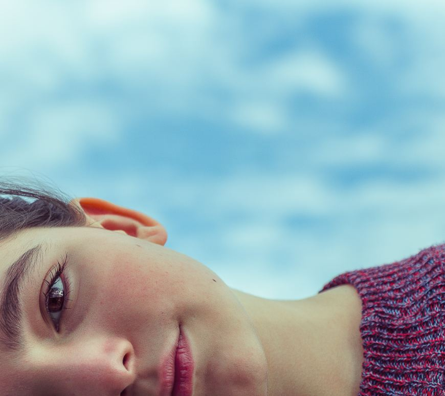A portrait picture of a girl cropped so that it only shows half her face, and shown horizontally.