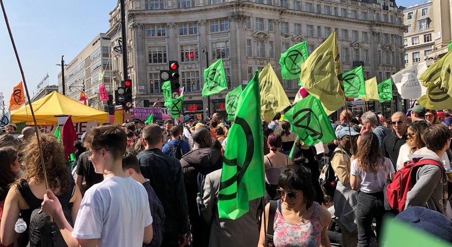 Extinction Rebellion protests at Oxford Circus. Lots of people with green XR flags.