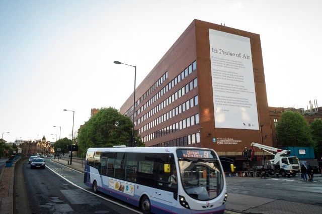 A university building in Sheffield covered with a big cloth with poetry written on it. A bus is in the foreground