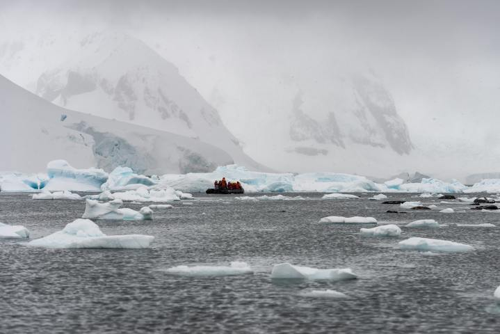 Small dingy full of people on the ocean surrounded by mountains of Antarctica