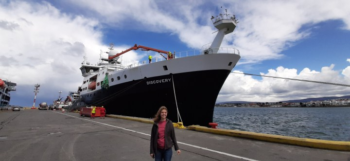 Ophelie standing on a dock in front of the research ship