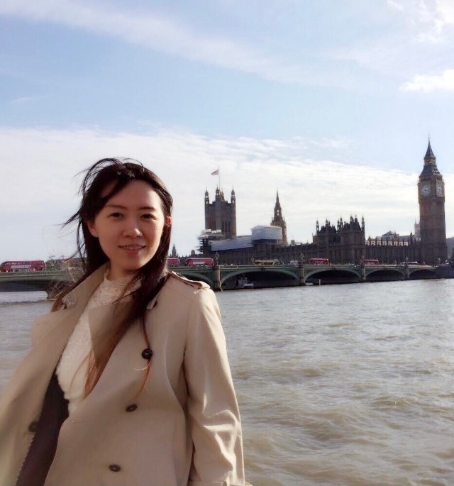 Dr Zhixuan Wang in London with the thames and the UK Parliament building in the background. She is wearing a beige coat and a white jumper and has long hair which is swept to the side by the wind.