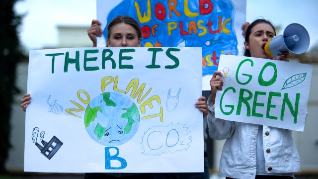Two young women protesting about the climate crisis. They are holding signed stating 'There is no planet B' and 'Go green'.