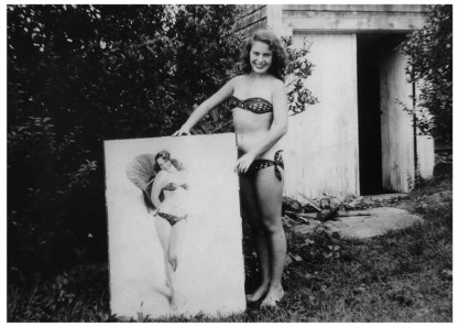 """Vera Bogach, model, posing with Armstrong's completed pastel """"Bikini Bound"""" (1949)"""